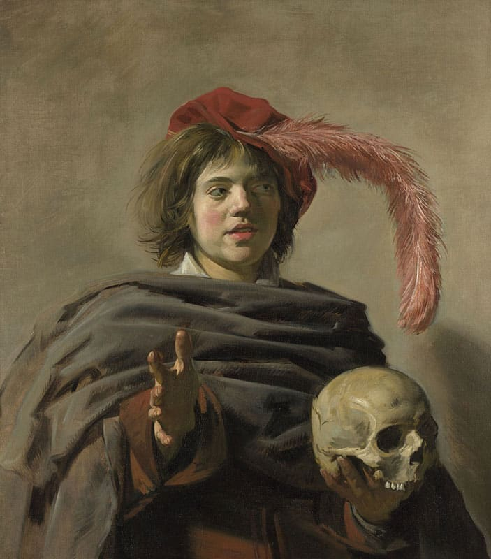 A young man holds as skull in his hand, looks out of frame and gestures with his hand.